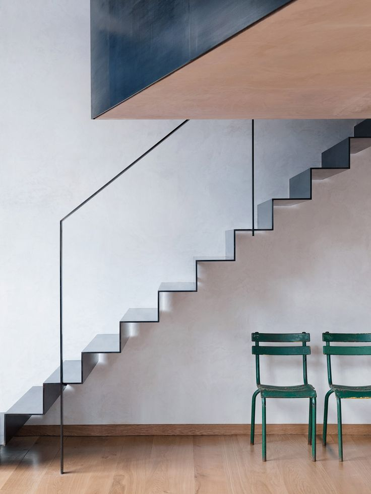 This photographer's home features a folded steel staircase, a mezzanine and wall-mounted storage for bicycles.