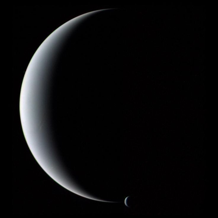 The crescent planet Neptune and its crescent moon Triton, as seen by NASA's Voyager 2 spacecraft in 1989.