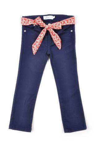 """Pantalón tipo """"jeans stretch"""" para niña, en color azul oscuro. Cinta roja con florecitas color hueso, alrededor de la cintura."""