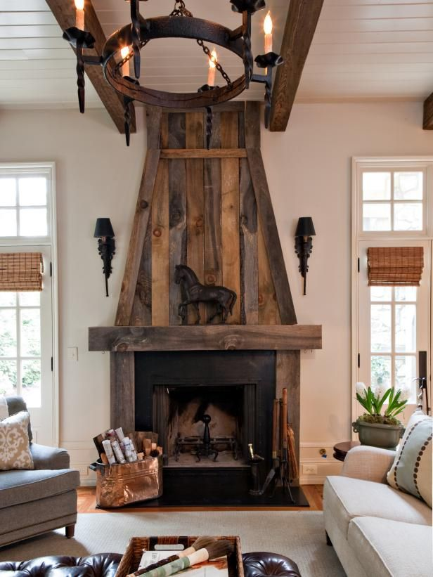 HGTV features a white transitional living room with a striking reclaimed-wood fireplace and matching chandelier.