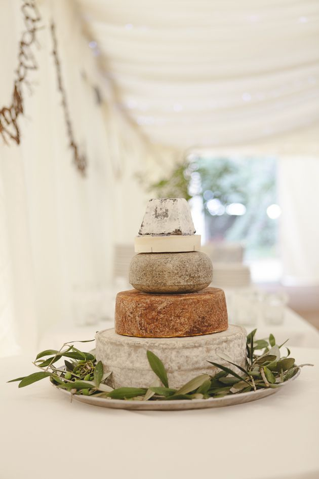 Italian inspired wedding reception. .cheese tower wrapped on olive branches ..serving the cheese of course!