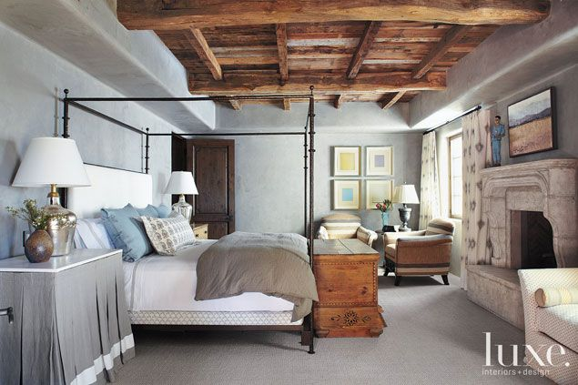 Soft gray walls are contrasted with reclaimed wood on the ceilings in the master bedroom of this Arizona villa.