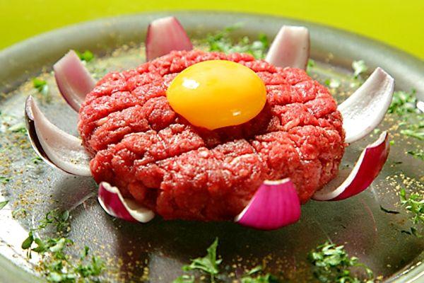 Na jemno umleté syrové hovězí maso, smíchané s šalotkami, hořčicí a dalšími ingrediencemi, servírované spolu s topinkami.