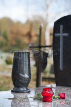 Каменный памятник с цветы и свечи на кладбище photo