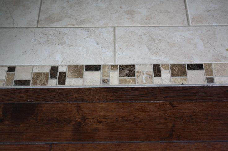 Guest bathroom tile floor to hallway hardwood transition.