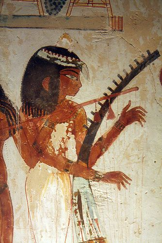 Lady harpist. Her instrument was most likely carved out of ebony wood, for the handle. The lute next to it, of a lighter wood, played by another woman, is decorated with red and yellow tassels. Their finger play is very graceful. 18th dynasty. Tomb of Nakht, TT52 , Sheikh Abd el-Qurna , Luxor. Egypt.