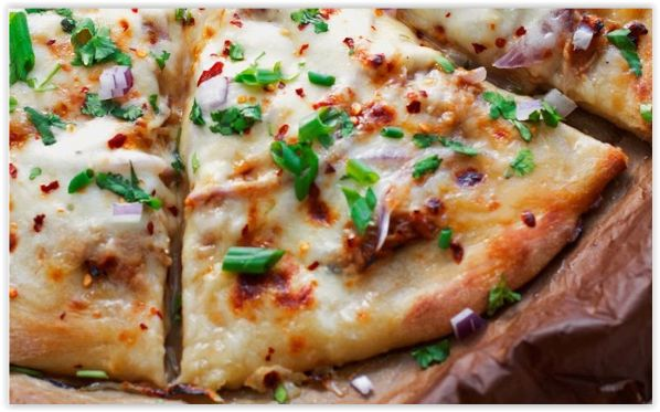 Pizza con pollo rostizado y bañada de salsa barbacoa, con cebolla roja, queso mozzarella y cebollino