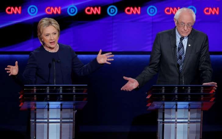 Democratic U.S. presidential candidate Hillary Clinton and rival Bernie Sanders speak simultaneously during the Democratic U.S. presidential candidates' debate in Flint, Michigan, March 6, 2016.