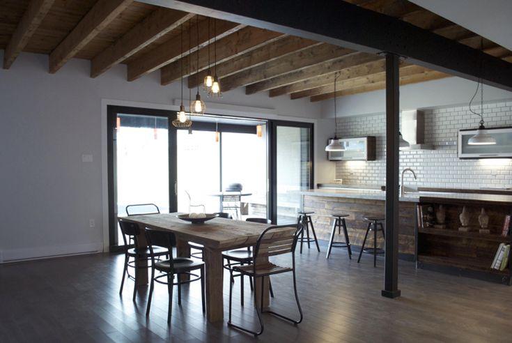 plafond en poutres apparentes à la française, îlot en bois et table à manger en bois massif dans la cuisine