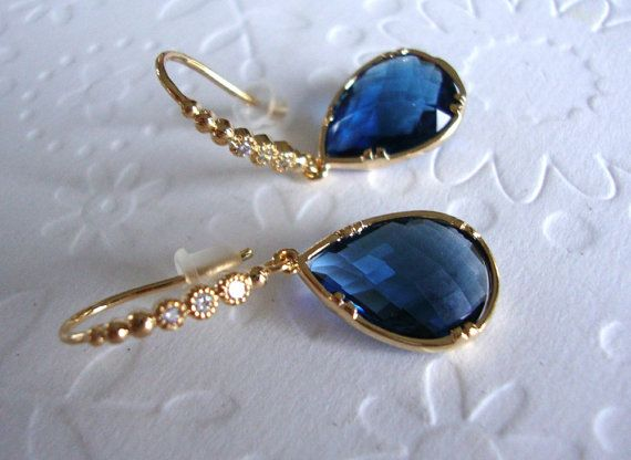 A beautiful faceted sapphire teardrop glass dangles from gold plated earrings with 3 inlaid cubic zirconias. Absolutely gorgeous earrings which will