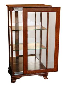 Amish Furniture Ohio Oak Sliding Door Curio Cabinet 175 is a fine example of Amish craftsmanship with two coats of a very durable finish after staining.NO veneers are used in the construction of the exterior of the cabinet, except for the outside back.It is ALL genuine oak or other hardwood panels.It has flat glass side panels and a flat glass front door which slides to the right when opened.The stylish legs and bottom finish molding add a degree of elegance to the Cabinet.The tw...