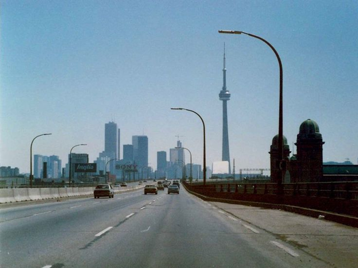 Toronto, Ontario, Canada, in 1989. That's the Gardiner Expressway travelling east with the CN Tower in the background. The building on the right with the two cupola roofed turrets is the Ricoh Coliseum on the grounds of Exhibition Place. In the Google Maps Street View the buildings on the left (north) are not seen in this archive picture…