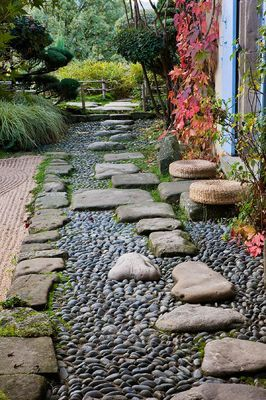 GARDEN OF ERIK BORJA, FRANCE: JAPANESE/ ASIAN STYLE - VIEW TO THE EAST SIDE OF THE HOUSE WITH BLUE SHUTTERS, PATH WITH PEBBLES AND ROCKS, GRAVEL GARDEN