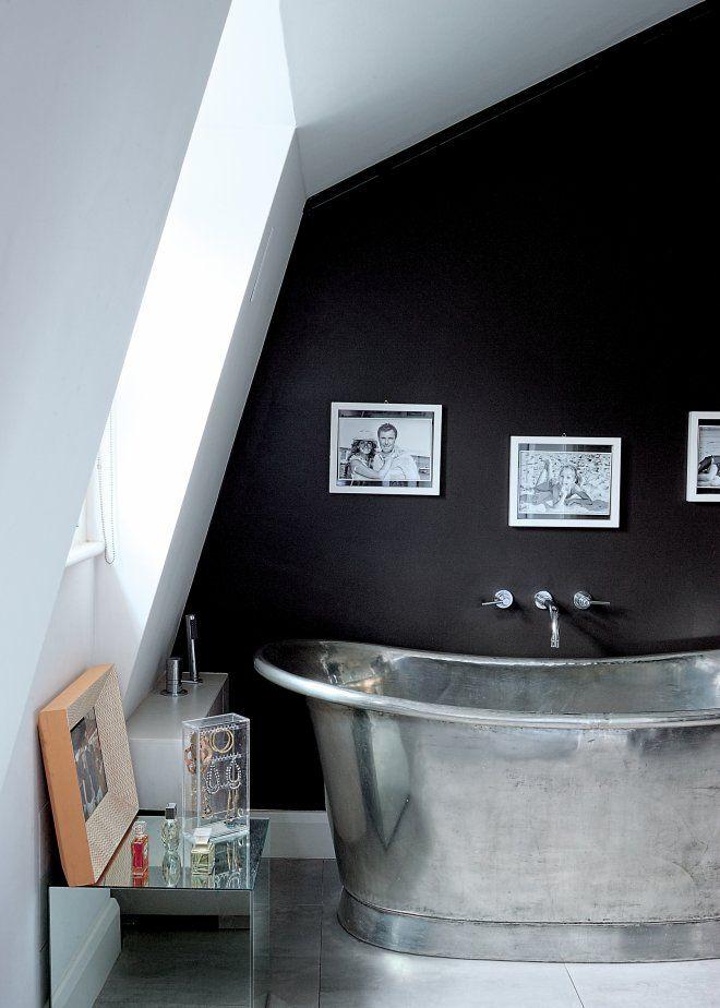Une salle de bain noire et blanche mansardée
