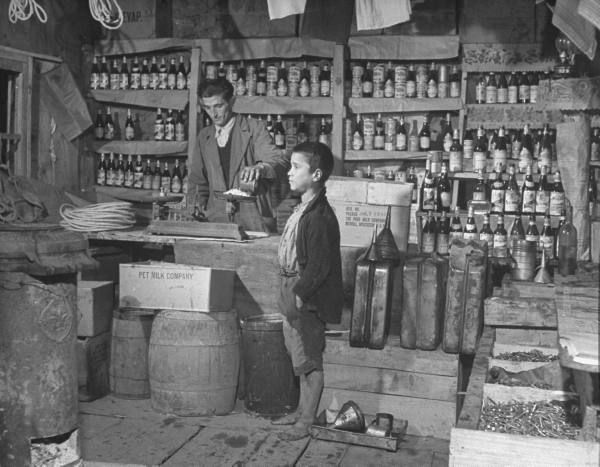 Civil War/Greece The storekeeper weighing beans that are to be sold to the small boy.Location:Louzesti, Greece Date taken:December 1947 Photographer:John Phillips