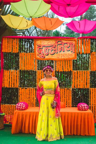 Mehendi Decor - Marigold Decor with Hanging Umberellas | WedMeGood | Bride in a Yellow and Pink Lehenga with Orange and Pink Decor #wedmegood #indianbride #indianwedding #bridalmehendi #mehendidecor #mehendioutfit #marigolddecor #orange #pink