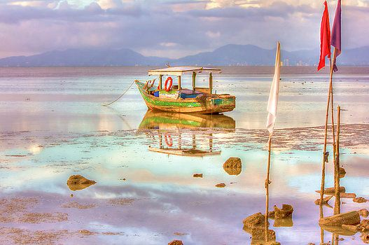 An old wooden fishing boat at low tide in a bay along the coastline of  the island of Trinidad in the Caribbean