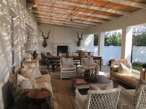 The Verandah has a very Colonial feel not sure about the Kudu hunting trophies flanking the fireplace.