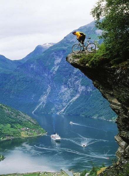 Mountain biker at Flydalsjuvet above Geiranger Fjord
