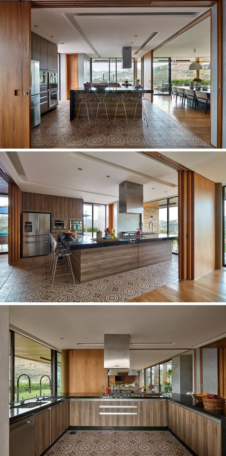 Wood walls open to reveal the kitchen and extends the living area of this modern house. Patterned tiles help to define the kitchen, while a black countertop contrasts the rich wood cabinets. #ModernKitchen #SlidingWoodWalls #InteriorDesign