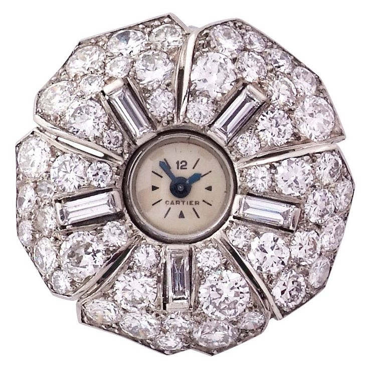 Diamond watch brooch by Cartier, French, c. 1930s. Centering on an annular watch-face applied with baton indicators and blue steel hands, within a flower head design, each raised petal set with a baguette-cut diamond within a pavé-set circular-cut diamond surround, watch face signed Cartier, the 16 jewel Swiss lever movement signed European Watch and Clock Co numbered 69675, case numbered 77466.