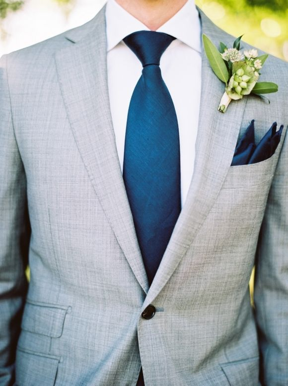 Navy blue tie and pocket sqaure with a gray suit for a wedding