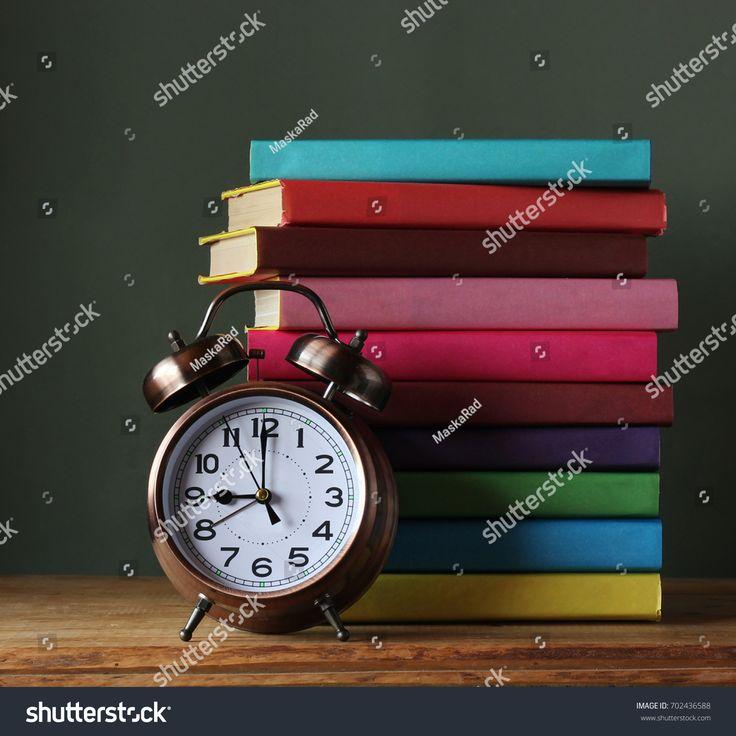 Стопка книг в разноцветных обложках и ретро-будильник бронзового цвета на столе. Книги. Обратно в школу. 1 сентября. День учителя.