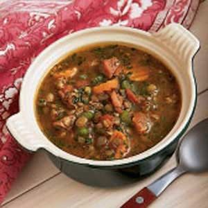 Ham and Lentil Soup Recipe  1 meaty ham bone  6 cups water  1-1/4 cups dried lentils, rinsed  1 can (28 ounces) diced tomatoes, undrained  2 to 3 carrots, sliced  2 celery ribs, sliced  1/4 cup chopped green onions  1/2 teaspoon salt  1/2 teaspoon garlic powder  1/2 teaspoon dried oregano  1/8 teaspoon pepper  12 ounces bulk pork sausage, cooked and drained  2 tablespoons chopped fresh parsley