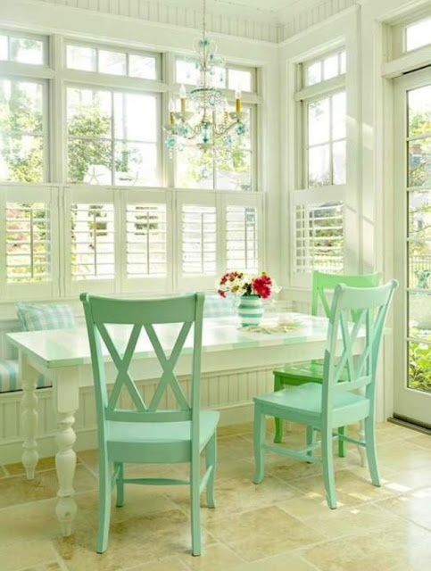 I love the windows, shutters, built in bench, and the farm table in this sunroom!