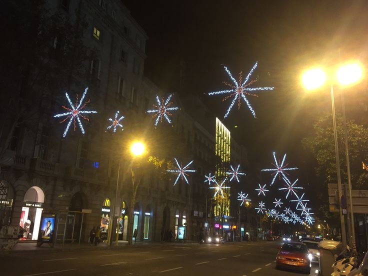 These snowflakes are located in Placa Catalunya. They contain red and white lights as they line up 3 in a row horizontally hanging over the street.