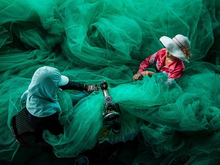 """Your Shot contributor Quang Tran was visiting the fishing village of Vinh Hy, Vietnam, when he came across these women sewing a fishing net. """"I knew their husbands fished for a living,"""" Tran writes. """"It's a typical image that everyone visiting the village would see. It expresses the life of the villagers, [as though they are] drifting in the ocean."""""""