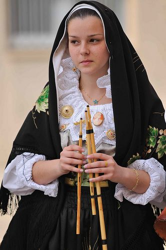 "Sardinian woman holding  ""Launeddas"" (a very old Sardinian flute-like musical instrument)"