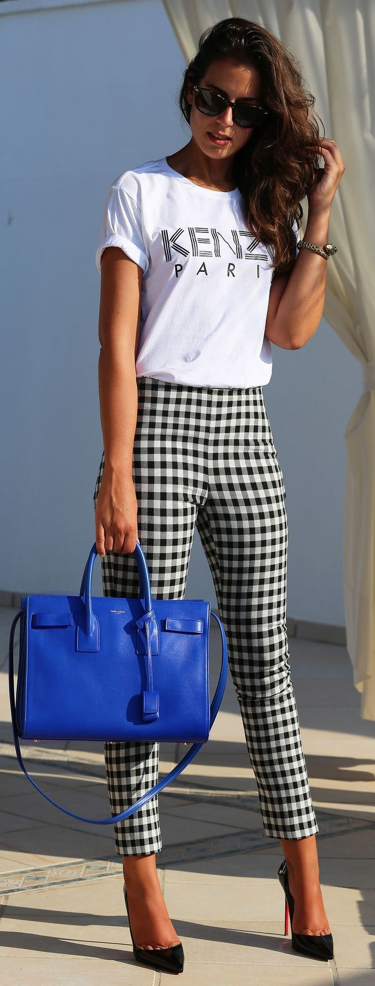 Rock a white and black print crew-neck t-shirt with black and white gingham fitted pants to effortlessly deal with whatever this day throws at you. Why not introduce black leather pumps to the mix for an added touch of style?   Shop this look on Lookastic: https://lookastic.com/women/looks/crew-neck-t-shirt-skinny-pants-pumps-tote-bag-sunglasses-bracelet/13452   — Black Sunglasses  — Gold Bracelet  — White and Black Print Crew-neck T-shirt  — Black and White Gingham Skinny Pants  — Blue…