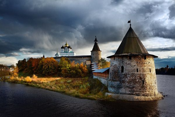 The photo is made at sunset. The sunset sun is shining on the domes and walls. The thunder-storm behind approaches. Russia. Pskov kremlin by Andrey Kuznetsov.