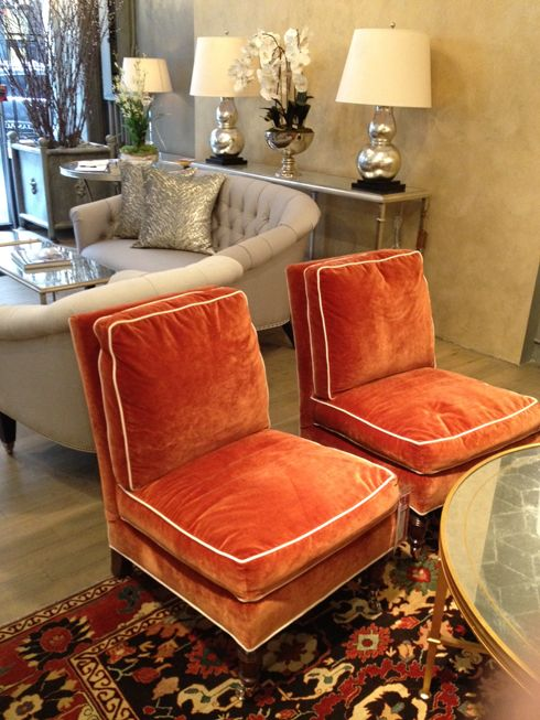 vintage-seeming orange velvet slipper chairs with white piping. Love. Lillian August store.
