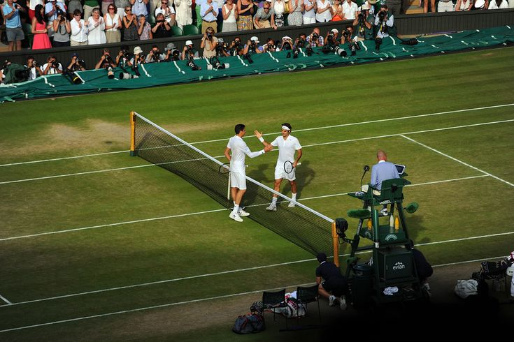 Milos Raonic and Roger Federer at the net after their match - Javier Garcia/AELTC
