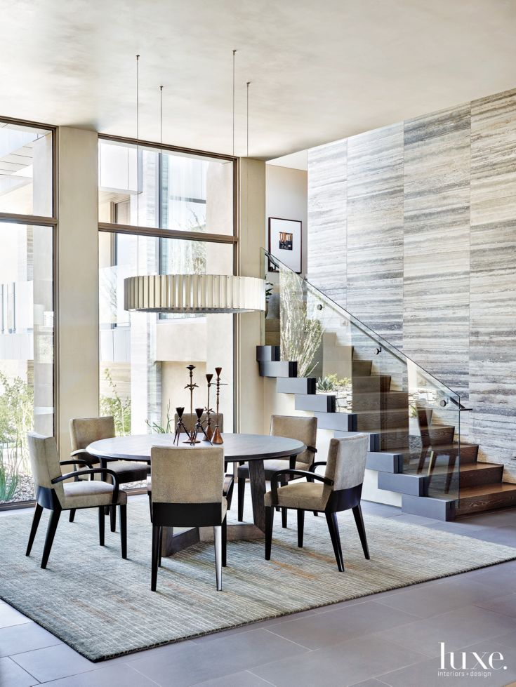 One side of the dining room is defined by the dynamic staircase. Dakota Jackson's Calypso chairs and the Gear ceiling fixture by McEwen Lighting Studio are all from Thomas Lavin in West Hollywood, California. The custom Quinn table by Joseph Jeup is from John Brooks Incorporated, and the rug is from Atelier Lapchi in West Hollywood.