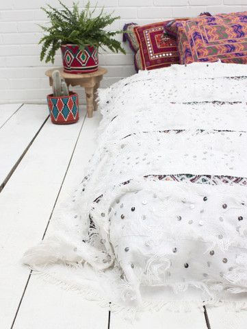 This stunning white and kilim vintage Moroccan wedding blanket is hand-woven of natural sheep's wool and cotton, decorated with strips of vintage kilim fabric and embellished with silver sequins and wool fringe.
