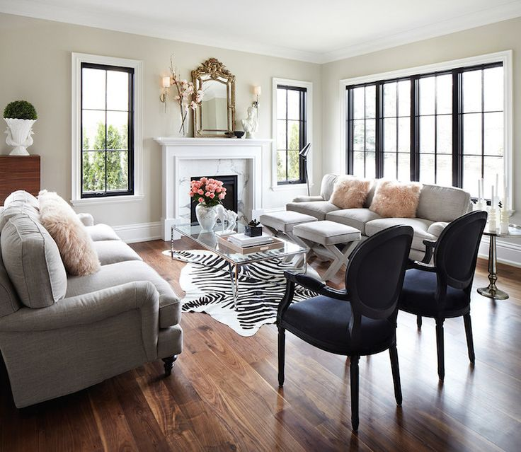 Chic living room features light grey, roll arm sofas accented with blush pink sheepkin pillows facing each other across from glass-top coffee table atop zebra cowhide rug paired with black velvet, round back chairs alongside traditional fireplace adorned with white marble surround topped with ornate mirror flanked by polished nickel sconces.