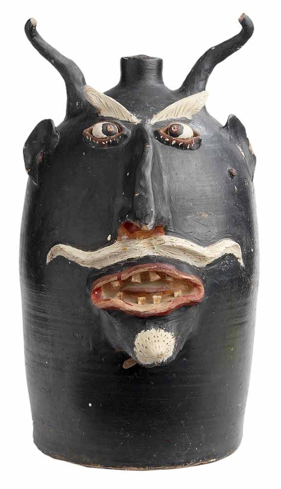 "Monumental Browns Pottery Devil Jug (attributed to Davis Brown, Arden, North Carolina, 1895-1967), largely black painted form with applied painted white eyes and inset red pupils, incised white eyebrows, mustache, and goatee, stamped at left shoulder ""Browns Pottery Handmade Arden, N.C."", 21 in.,  One of only a few examples known of this form and make.  Provenance: Sewell Collection, Georgia,  Brunk, 01/28/2017, est $3,000 - $6,000"