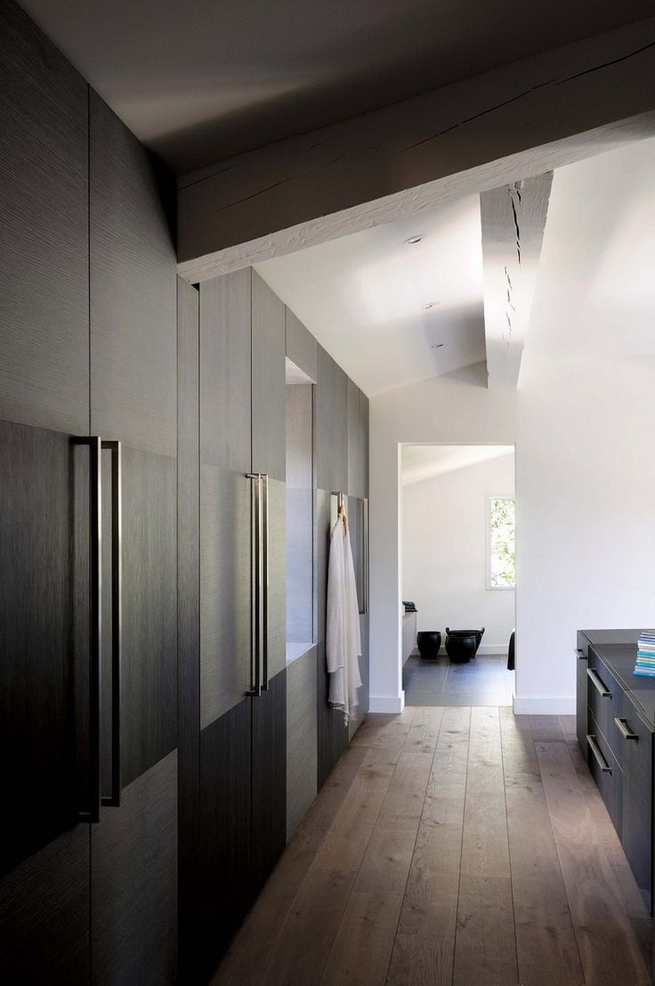 Spare dressing area, clean lines, slab  doors with alternating grain direction, vintage wood floors