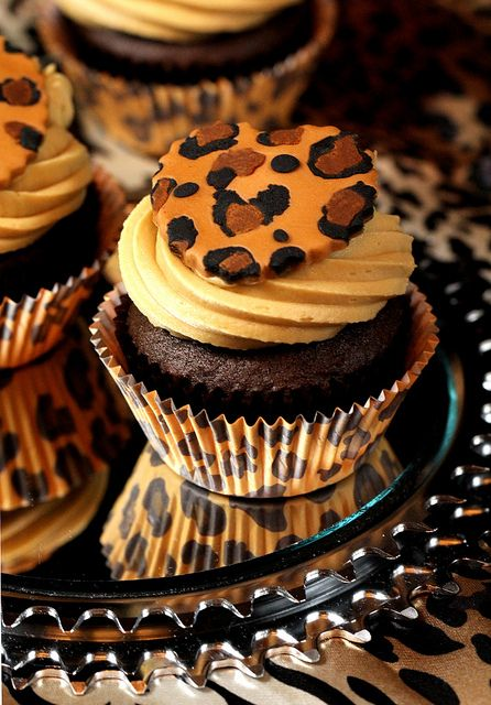 Swirly frosting cupcakes with cheetah print scalloped medallions and cupcake liner.
