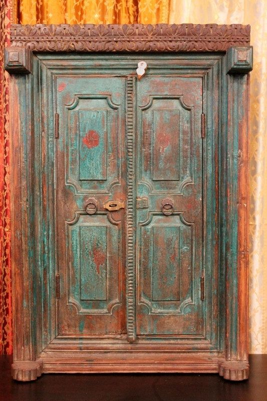 """This 19th century Indian window shutter is from Rajasthan, India. It has been repurposed into a truly unique mirror! It is made of very thick, solid, teak wood with original finish and latch. The details, including the header were all hand carved and are just stunning. The distressed painted green and red finish is original. We've installed a high quality 1/4"""" mirror. Rustic Distressed Hand by hammerandhandimports,"""
