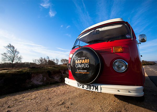 """A 1974 RHD Westfalia camper van, Berry has had a real transformation, with a complete re-spray, new leather upholstery and a new engine rebuild carried out by our restoration team. She's a real """"head turner"""" and loves to show off her sparkling new red livery making everyone stop and stare. The classic Westfalia roof sleeps 2 children and the large full width rock and roll bed sleeps 2 adults. Award Winning Classic VW Campervan Hire from New Forest Safari Campers - The best way t..."""