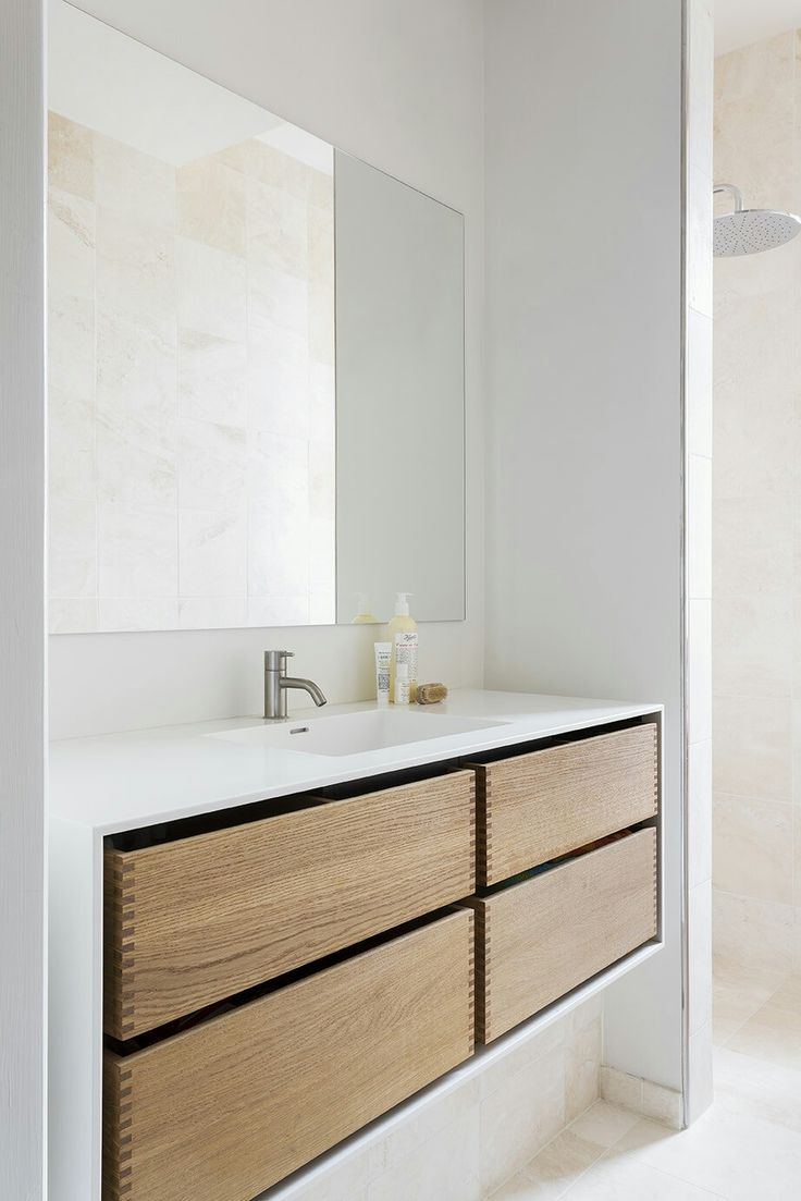 Simplicity, minimalism, and functionality are all part of the unique Scandinavian style. This aesthetic made-to-measure bathroom furniture embraces it all. The massive oaken drawers are encased in a shell of Corian with an integrated sink. See more bespoke furniture at www.bynordichands.ch