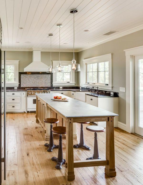 trois lampes pendantes au-dessus d'un grand comtptoir de cuisine, plafond bois blanc et une hotte blanche