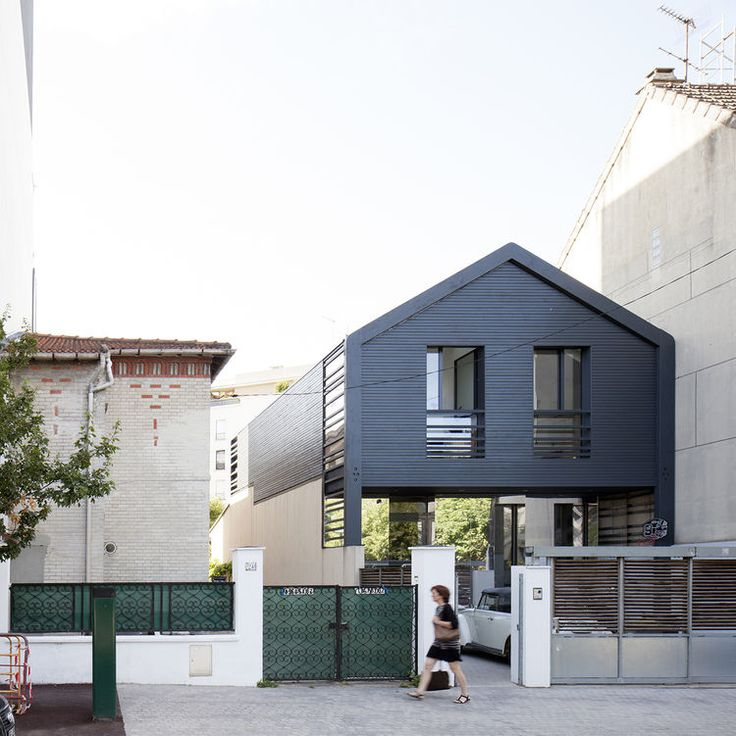 Painted-black larch facade of prefab extension by Djuric Tardio Architectes.