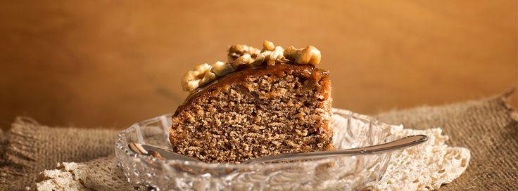 Σταφιδοκέικ: Κέικ λαδιού με ξανθή σταφίδα και άρωμα κανέλα και επικάλυψη μαρμελάδας πορτοκάλι σε ξύλινο πυρίμαχο σκεύος.