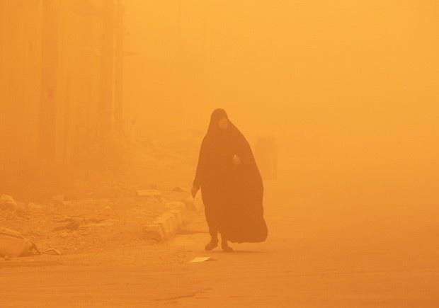 Mulher caminha em meio à tempestade de areia (Foto: Sabah Arar/AFP)