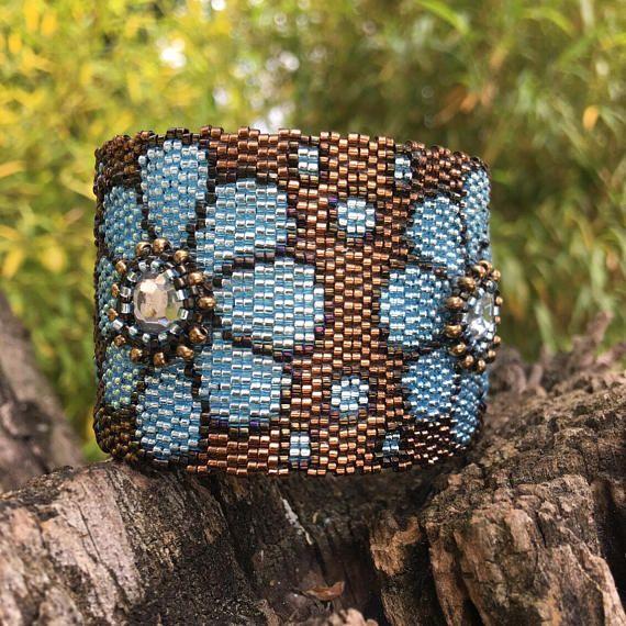 Modello a forma di fiore con nel centro un cristallo strass circondato da petali blu cielo di perle oro antico-basato. I fiori sono su un fondo di cioccolato metallico (riflessioni in ottone) Tessuto con miyuki borda il braccialetto Perline Miyuki sono di conteria, 1 mm, molto alta qualità. Sono tessuti con un ago, lavoro di pizzo reale. Limpressione visiva è spesso visto come un tessuto luccicante. Questa tessitura dà un braccialetto molto flessibile da indossare, come una seconda pelle…